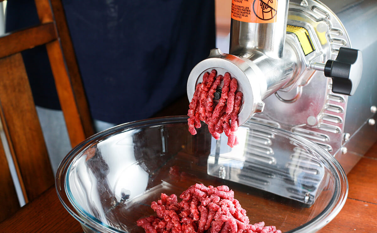 Commercial meat grinder in use